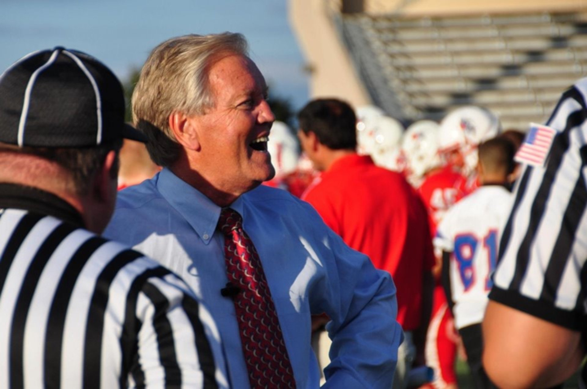 Ross Hjelseth smiles on the sideline of a football game in front of two referees.