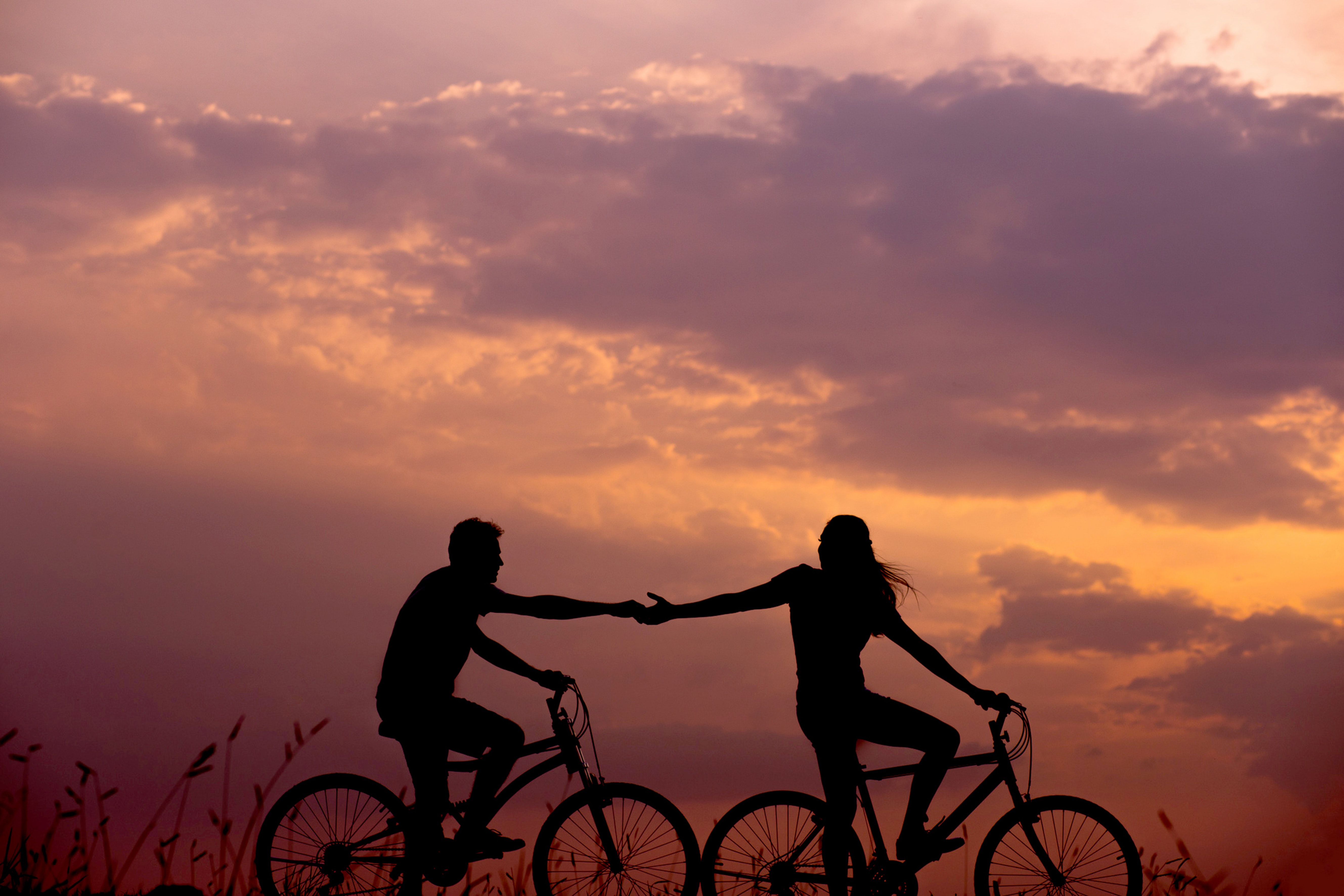 A woman on a bike reaches out to help a man on another bike while they both ride under a beautiful, orange tinted sky.,