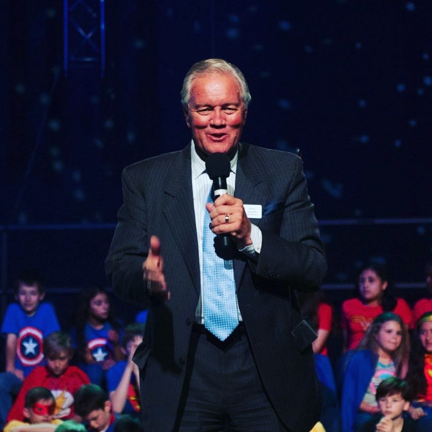 Ross Hjelseth speaks to a group of children at an event.