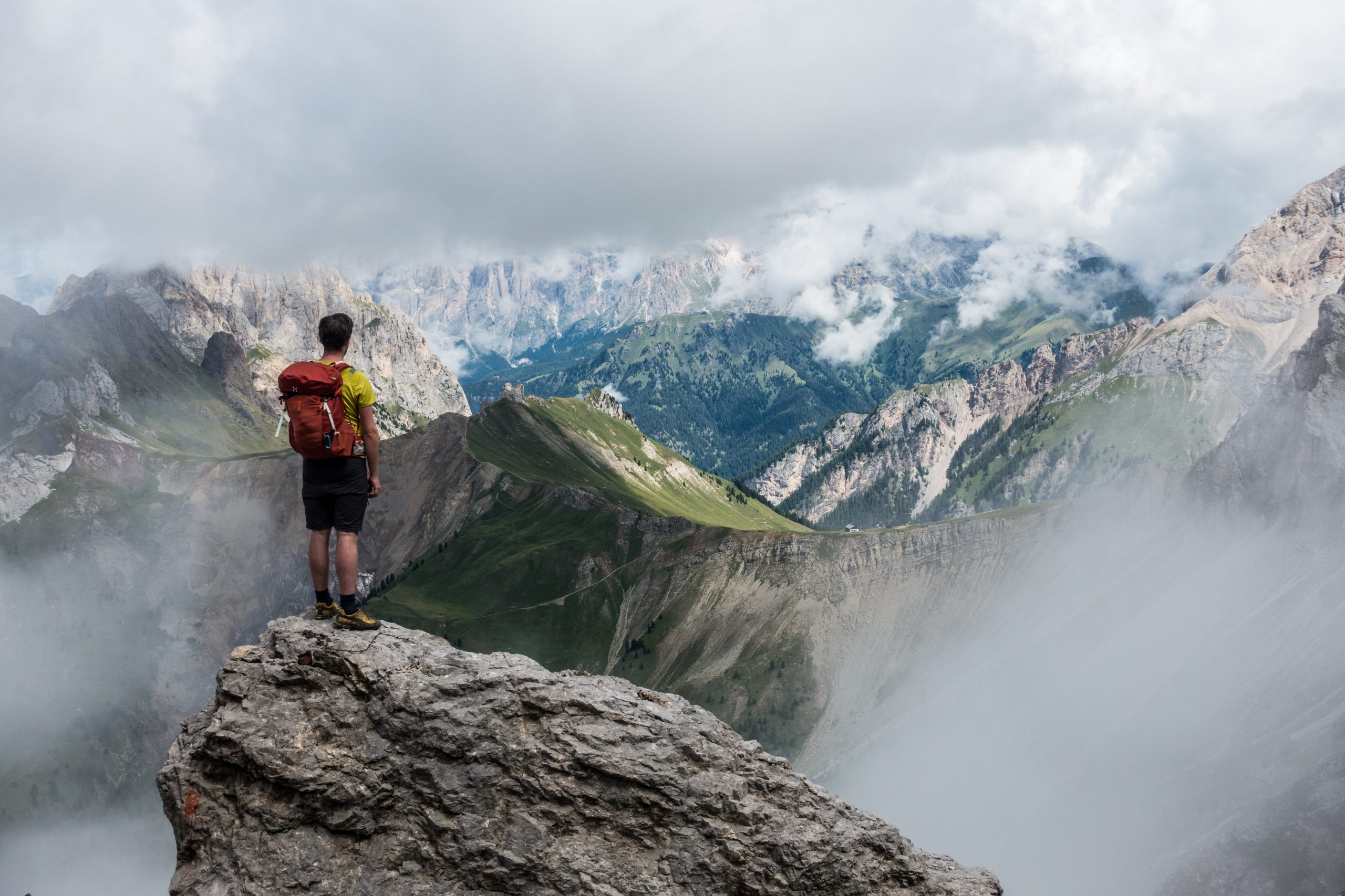 Man with backpack stands on the edge of a cliff looking out over a gorgeous and vast mountainscape.