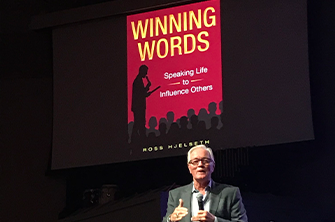 Ross Hjelseth gives a talk on stage while the cover for his book Winning Words is seen overhead.