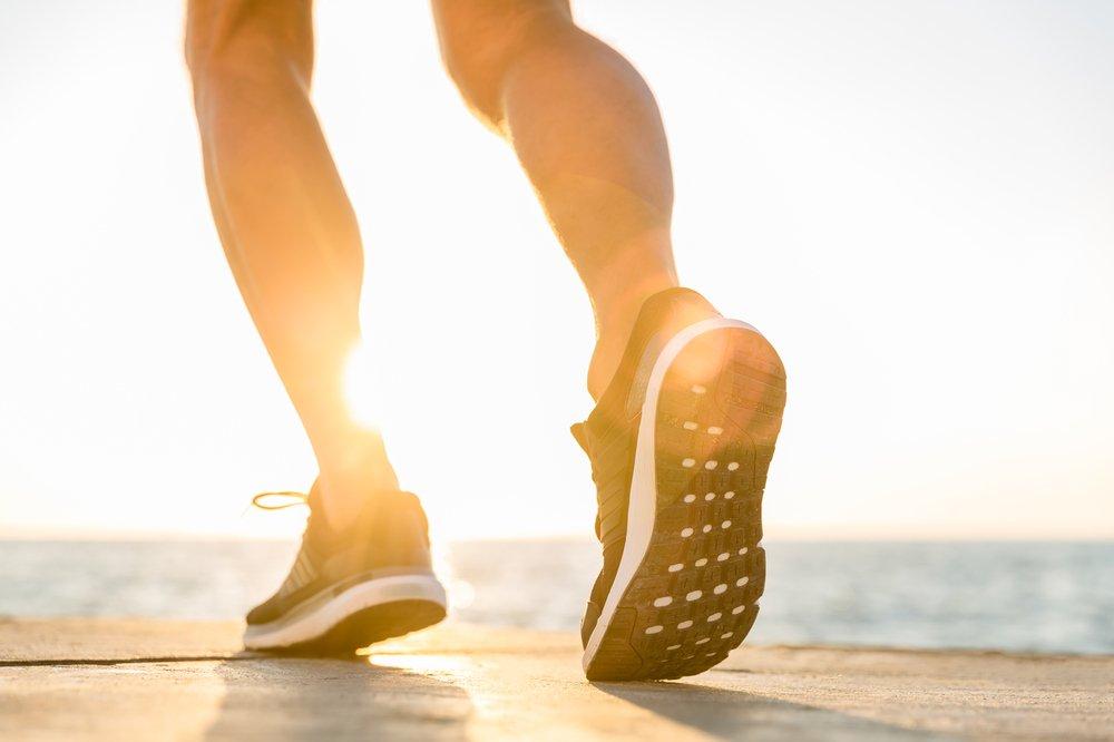 Man's legs and feet prepare to run on sunny beach.
